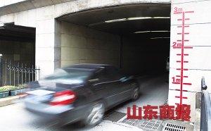 """汽车驶进郑州市正兴街一处用红线标注""""水位警戒线""""的下穿隧道。"""