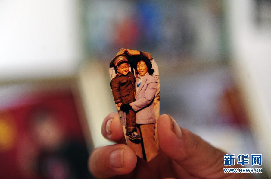8月2日,吕小军的母亲王爱萍在整理吕小军的成长照片。