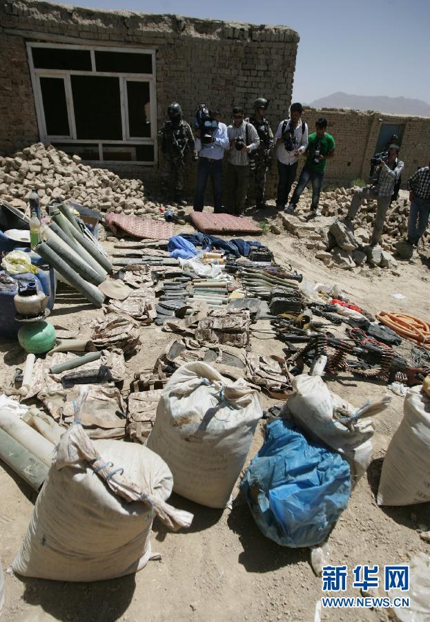 8月2日,阿富汗安全部队人员在喀布尔的突袭行动现场展示缴获的武器弹药。