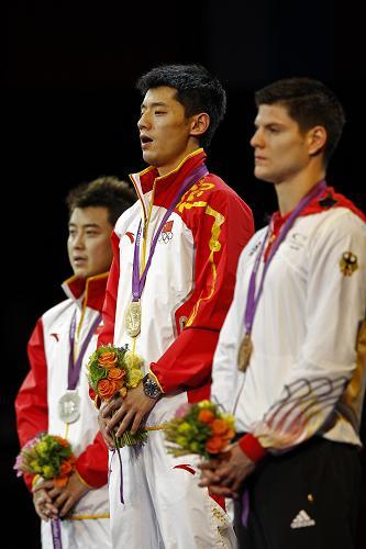 8月2日,张继科(中)、王皓(左)在领奖台上唱国歌。当日,在2012伦敦奥运会乒乓球男单决赛中,中国选手张继科以4比1战胜队友王皓,夺得冠军。新华社记者 沈伯韩 摄