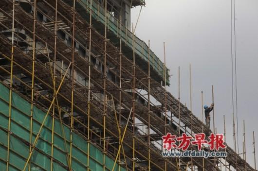 上海金沙江路中山北路,一位建筑工人正在加固脚手架。早报记者 高征 图