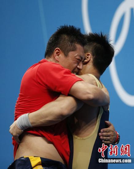 当地时间8月1日,在伦敦奥运会男子举重77公斤级决赛中,中国选手吕小军打破自己保持的世界纪录,拿下中国队的第16块金牌。图为吕小军与教练拥抱。记者 盛佳鹏 摄