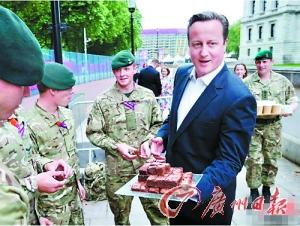 3日,英国首相卡梅伦端着布朗尼蛋糕分给奥运安保的士兵。资料图片