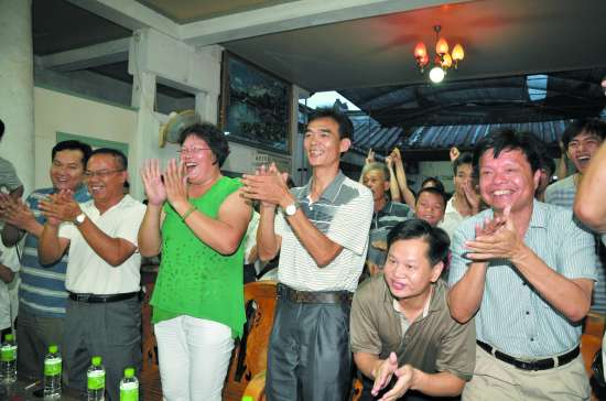 黄文仪父母左三、左四为女儿欢呼鼓掌。 本报记者 袁笙 摄