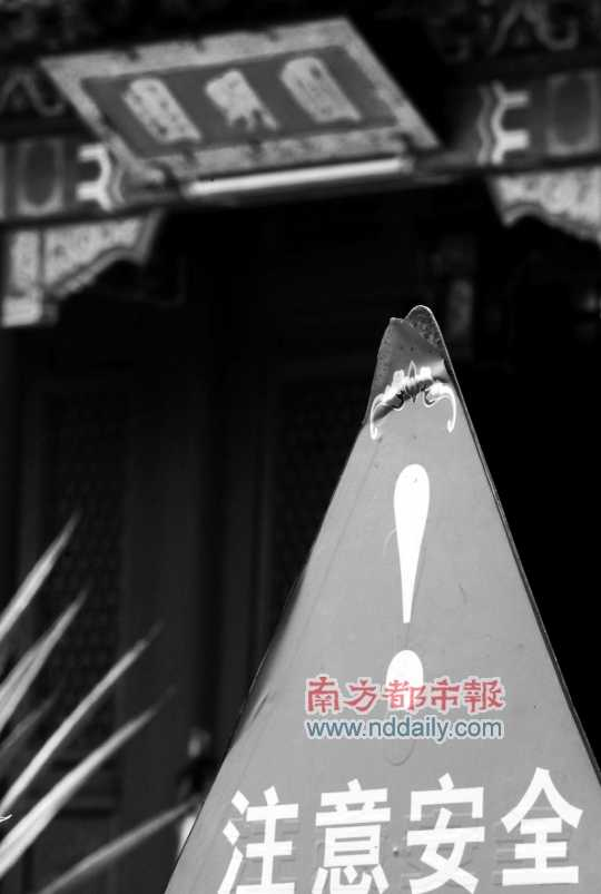 陈坤荣/圆明园内,一块略有损坏的警示牌立在大堂前,提醒游客留意水深...