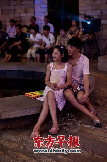 广场公园,一对父女观看露天电影。 杨深来 早报资料