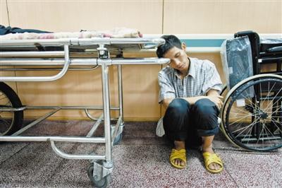 积水潭医院,陆永波靠着杨丽的推车蹲在走廊边。
