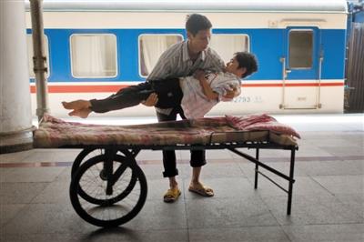 """北京西站,下车后,陆永波把女友杨丽抱上自制的手推车,""""5年前,我花了500元钱叫人焊上的。""""陆永波介绍。本版摄影/实习生 杨奉焓"""