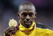 奥运图:博尔特获颁百米金牌 展金牌