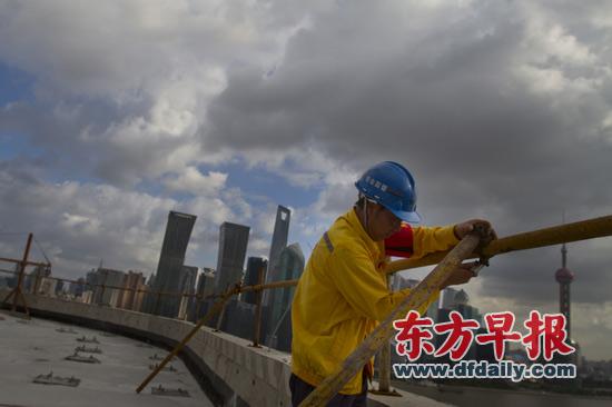 昨日,上海国际航运服务中心工地,一位工人对脚手架进行加固措施。早报见习记者 杨深来 图