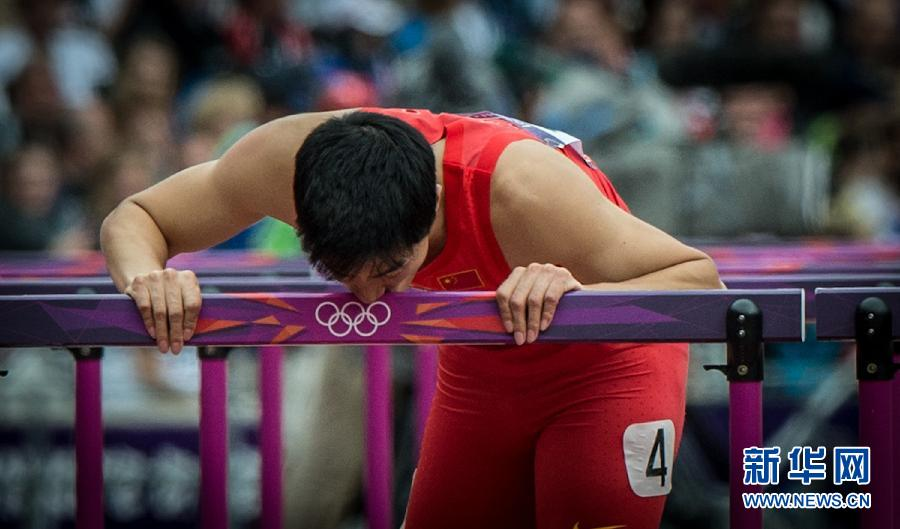 8月7日,中国选手刘翔摔倒后单脚跳完成比赛,亲吻跨栏。当日,刘翔在伦敦奥运会田径男子110米栏预赛中摔倒,无缘晋级。 新华社记者杨磊摄