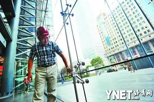 工作人员检查玻璃幕墙的配件和安装