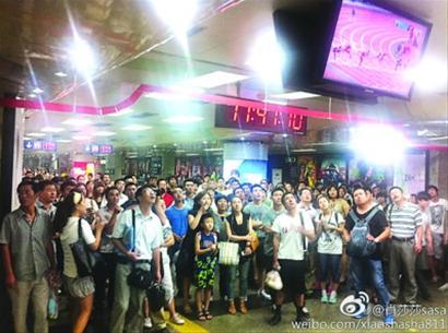 北京的地铁站内,人们纷纷驻足观看电视直播