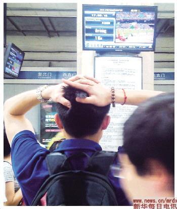 8月7日,一名男子在北京地铁2号线雍和宫站观看比赛,为刘翔的遗憾出局抱头惋惜(手机拍摄)。