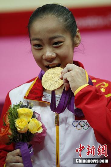 当地时间8月7日,伦敦奥运体操女子平衡木比赛,中国选手邓琳琳以15.600的成绩夺得冠军。图为邓琳琳咬金庆祝。记者 盛佳鹏 摄