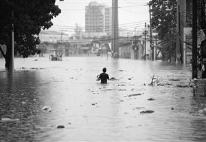 在马尼拉郊区,一名市民涉水走过洪水泛滥的街道