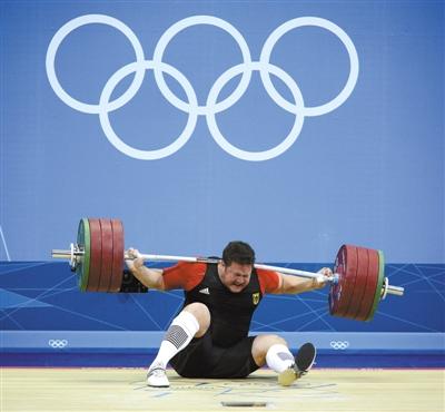 """在伦敦奥运的举重台上,卫冕冠军、德国选手马蒂亚斯·施泰纳因抓举失败,而不幸被杠铃砸中,这天上掉下的""""铃妹妹""""使其被迫退出比赛,告别奖牌。"""