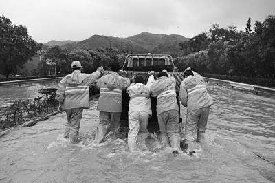 8月8日,在浙江省象山县西周镇莲花村,公路抢险人员奋力将涉水熄火的车辆推出积水路段。
