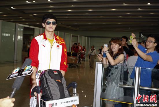 8月6日,伦敦奥运会游泳冠军孙杨到达首都机场,受到粉丝们的热捧。中新社发 张浩 摄