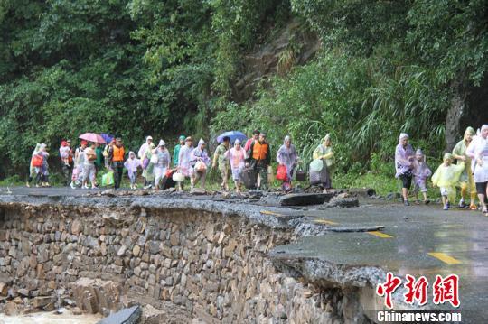 图为武警官兵带着旅客经过塌方山路。完何元洪摄