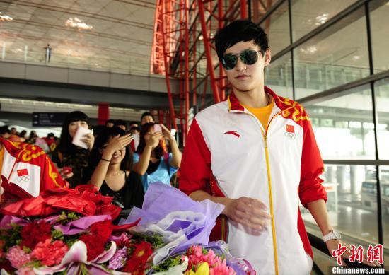 8月6日,在伦敦奥运会上夺得男子1500米自由泳、400米自由泳金牌,共计夺得2金1银1铜的中国选手孙杨随中国游泳队乘机返回北京,在机场受到粉丝的热情追捧。中新社发 侯宇 摄