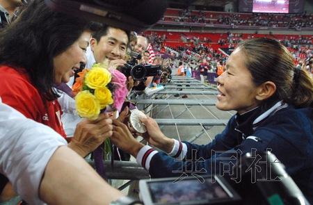 日本女足8月9日在伦敦奥运会上夺得银牌后,队员泽穗希(右)给母亲满寿子戴上了奖牌。(共同社)