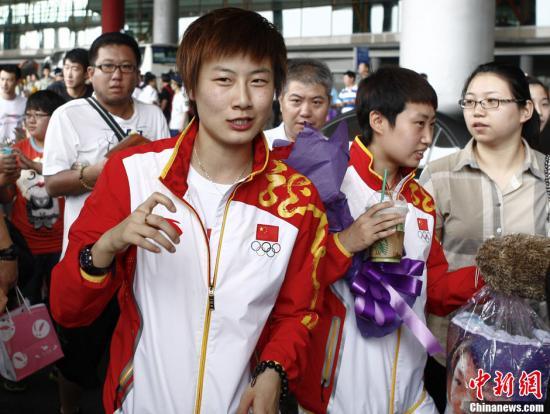 8月10日,伦敦奥运会中国代表团的乒乓球和女排队回国,图为乒乓球奥运女子团体冠军成员丁宁在机场抿嘴微笑,后面则是端着奶茶的郭跃。中新社发 张浩 摄