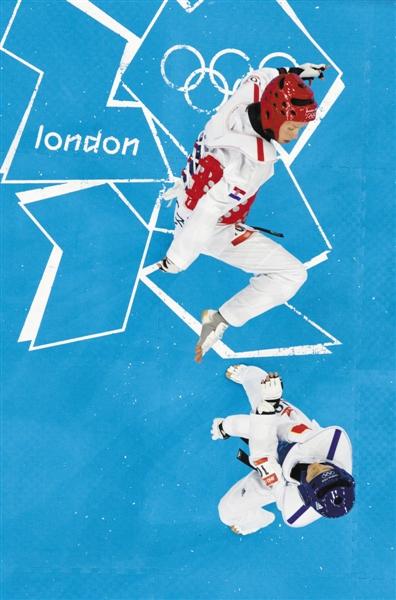 伦敦奥运会成功蝉联冠军后,吴静钰举起国旗庆祝胜利。