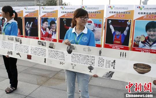 """8月12日,志愿者在北京奥林匹克公园里展开""""《奥林匹克宣言》美丽的奥林匹克文化长卷"""",他们背后正是伦敦奥运会中国冠军榜。中新社发 张浩 摄"""