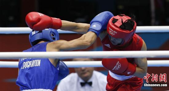 当地时间8月11日,在伦敦奥运会男子拳击49公斤级的决赛中,中国名将邹市明击败泰国老将庞普里亚杨,实现奥运会的卫冕,庞普里亚杨获得银牌。图为邹市明(红)在比赛中。记者 盛佳鹏 摄