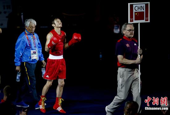当地时间8月11日,在伦敦奥运会男子拳击49公斤级的决赛中,中国名将邹市明击败泰国老将庞普里亚杨,实现奥运会的卫冕,庞普里亚杨获得银牌。图为邹市明入场。记者盛佳鹏