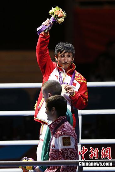 当地时间8月11日,在伦敦奥运会男子拳击49公斤级的决赛中,中国名将邹市明击败泰国老将庞普里亚杨,实现奥运会的卫冕,庞普里亚杨获得银牌。图为邹市明领奖。记者 盛佳鹏 摄