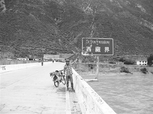 图为:谭耀骑行抵达西藏界时的留影