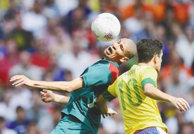 8月11日,在伦敦奥运会男子足球决赛中,墨西哥队球员恩里克斯(左)与巴西队球员奥斯卡在比赛中争顶头球。