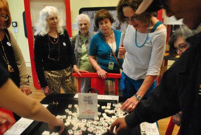 """洛杉矶Skirball博物馆(Skirball Cultural Center)推出""""千古奇观""""麻将展,讲解员为参观团亲自示范如何玩麻将。(美国《世界日报》/张敏毅摄影)"""