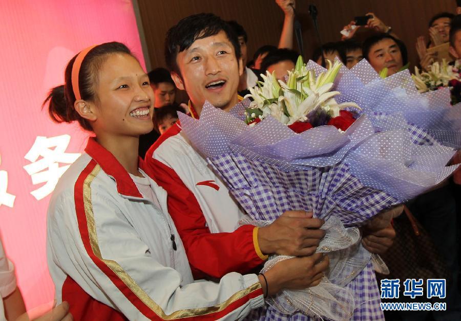 8月18日,邹市明(左)和妻儿走出机场。当日,伦敦奥运会拳击冠军邹市明回到家乡贵州,大批拳迷、体育迷赶到贵阳龙洞堡机场接机欢迎邹市明凯旋归来。 新华社记者刘续摄