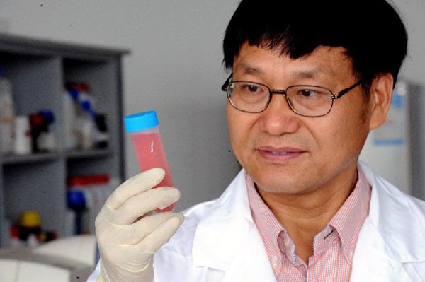 8月16日,张学记教授在做合成纳米粒子溶液实验。新华社记者 何俊昌 摄