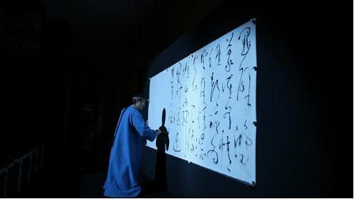 """李斌权(饰曹雪芹)在""""2012梦幻水立方――大型水景秀《红楼梦》""""挥毫"""