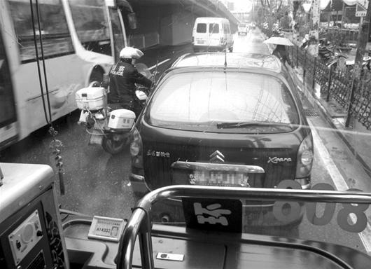 江城/楚天金报讯图为:违停车辆导致路面堵车,交警前来处理资料图片