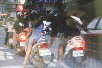 右方摩托车上的男乘客突然拉走女子置于脚踏垫上的皮包。图片来源:台湾《联合报》