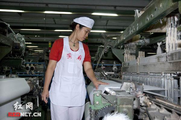 周茶秀/(周茶秀在纺织车间检查着每一台设备的工作状况。)