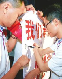 8月21日,成都市锦江剧场,失去双手的杨尔聪用双臂夹着笔签名。