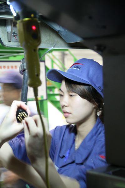图三:南车女员工参与组装地铁列车。