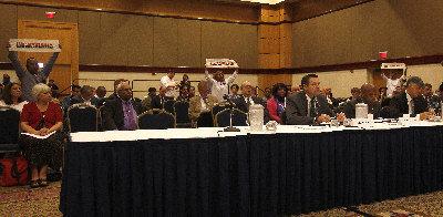 """堪萨斯州州务卿柯巴克(前排左一)日前在亚拉巴马州伯明翰的移民听证会发言,多名高举写有""""无证""""牌子的示威者在场抗议。(美国《世界日报》援引美联社)"""