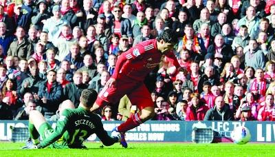 利物浦头号前锋苏亚雷斯(红衣),将再度挑战门将斯泽斯尼(绿衣)领衔的阿森纳后防。