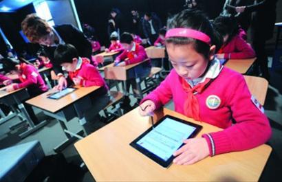 """嘉定区实验小学""""苹果班""""的学生使用的iPad都是家里现有的,而去年卢湾一小学生使用的iPad则由校方提供。图为卢湾一小学生用iPad上课。"""