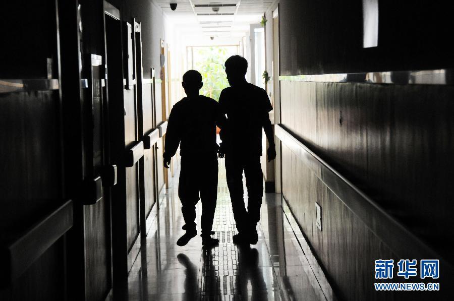 老师 晓亮/9月6日,陈晓亮右搀扶一名做完康复训练的智障学生返回教室。