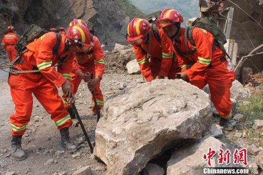 武警云南总队第三支队地震应急救援官兵清除路障,撬运堵在路上的石块。盛敏摄