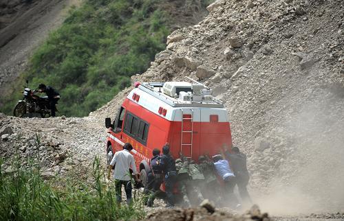 9月9日,一辆救援车辆前往重灾区洛泽河镇的山路倪家岩塌方路段,众人推车帮助车辆前行。新华社记者 秦晴 摄