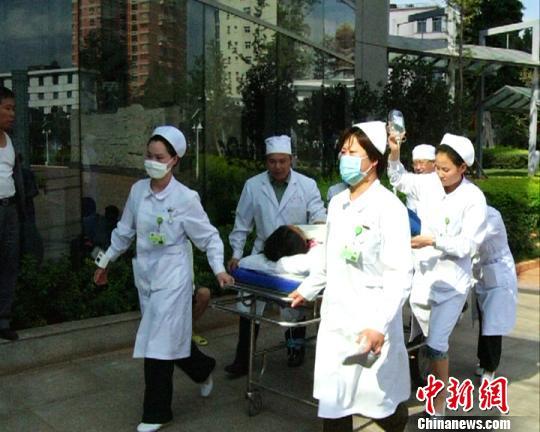 图为解放军昆明总医院女兵给受伤小女孩喂水杨华伟摄